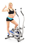 Woman giving a thumb up on a cross trainer machine Stock Photos