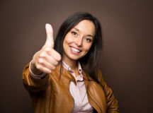 Woman giving thumbs up approval hand sign gesture smiling. Happy isolated on white background in full body length in high angle perspective view. Content smile stock photos