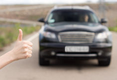 Woman giving a thumbs up as she stands hitchhiking Royalty Free Stock Photo