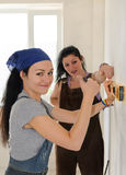 Woman giving a thumbs up while renovating. Pretty young women giving a thumbs up of approval and success while renovating an apartment with a friend who is Stock Photography