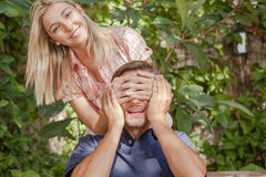 Woman giving to her boyfriend a surprise. Pretty women giving to her boyfriend a surprise Stock Images