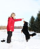 Woman giving treats to dog. Woman giving treats to her dog during a winter day stock photo