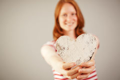 A woman giving a wooden heart Stock Images