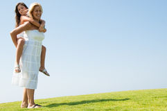 Woman giving young girl piggyback ride Stock Photo