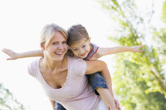 Woman giving young girl piggyback ride smiling