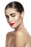 Woman with glamour red lips make-up, clean skin. Smiling and winking. Close-up portrait of sexy caucasian young model with glamour red lips make-up. Perfect Stock Photography