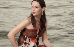 Woman glancing away. Woman in a fashionable dress looking away with water in the background Stock Image