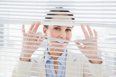 Woman glancing through some blinds Stock Image