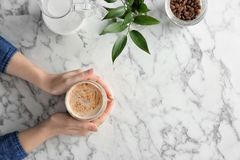 Woman with glass of aromatic hot coffee at marble table,. Top view Royalty Free Stock Photo