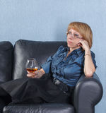 Woman with a glass brandy on couch Royalty Free Stock Image