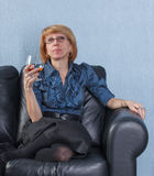 Woman with a glass brandy on couch. Portrait of relaxed middle aged woman with a glass brandy on couch stock image