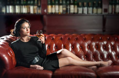 Woman with a glass of brandy on the sofa Stock Photo