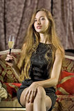 Woman with glass of brut. Beautiful woman on a sofa with glass of brut royalty free stock photography