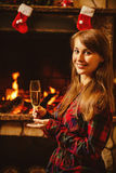 Woman with a glass of champagne by the fireplace. Young woman si royalty free stock photos