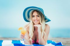 Woman with glass of cocktail in hand lying on sand beach stock images