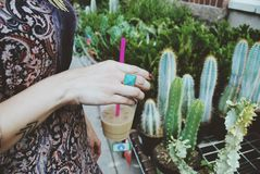 Woman with glass of coffee next to cactus stall Stock Photography