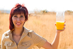 Woman and a glass of juice. Woman in a field and a glass of orange juice Stock Photos
