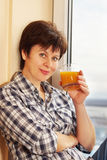 Woman with a glass of juice sits near the window Royalty Free Stock Photography