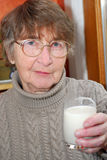 Woman glass milk. Elderly woman holding a glass of milk in her hand Stock Photo