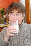 Woman glass milk. Elderly woman holding a glass of milk in her hand Stock Images