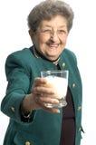 Woman with glass of milk. Smiling senior citizen woman with glass of fresh healthy milk royalty free stock photos