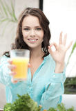 Woman with glass of orange juice showing ok sign Stock Photo