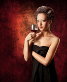 Woman with glass of red wine on grunge background. Beautiful woman with glass of red wine on grunge background. Looking at camera. Low key Stock Images