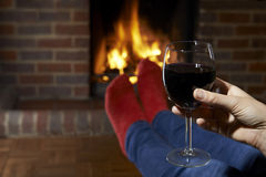 Woman With Glass Of Red Wine Relaxing By Fire Royalty Free Stock Photos
