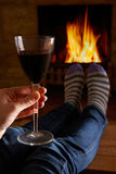 Woman With Glass Of Red Wine Relaxing By Fire Royalty Free Stock Image