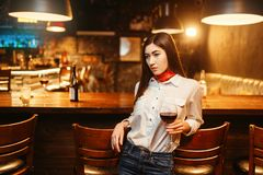 Woman with glass of red wine at wooden bar counter. Young attractive woman with glass of red wine at wooden bar counter. Female customer leisures in pub stock photo