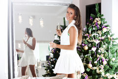 Woman with glass of sparkling wine over christmas tree lights ba Stock Image