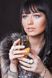 Woman with glass of sparkling wine. Portrait of a gorgeous young brunette with glass of sparkling wine on the black background Stock Images
