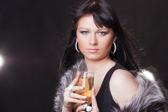 Woman with glass of sparkling wine. Portrait of a gorgeous young brunette with glass of sparkling wine on the black background Stock Image