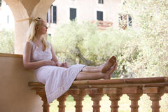 Woman with glass of water sitting on balcony railing with eyes closed royalty free stock photo