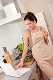 Woman with glass of white wine in the kitchen Royalty Free Stock Image