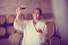 Woman with glass of wine in cellar Stock Photo