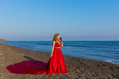 Woman with a glass of wine and sea. Beautiful woman with a glass of wine is on the shore of the sea royalty free stock image