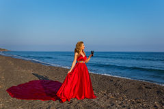 Woman with a glass of wine and sea. Beautiful woman with a glass of wine is on the shore of the sea royalty free stock photography