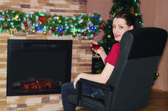 Woman with glass of wine  sitting near the fireplace Stock Images