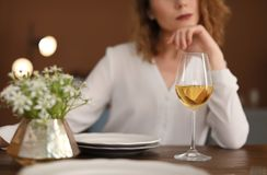 Woman with glass of wine at table in restaurant. Professional sommelier stock photo