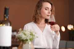 Woman with glass of wine at table in restaurant. Professional sommelier stock images