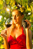 Woman with glass of wine in vineyard. Woman with glass of wine in the vineyard with sunshine, she is the wine queen Royalty Free Stock Image
