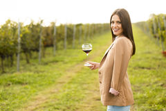 Woman with glass of wine in vineyard. Vintner woman check red wine in a vineyard Stock Photo