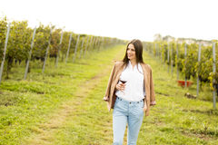 Woman with glass of wine in vineyard. Vintner woman check red wine in a vineyard Stock Photos