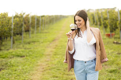 Woman with glass of wine in vineyard. Vintner woman check red wine in a vineyard Royalty Free Stock Photography