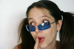 Woman with glasses. A studio portrait of a beautiful caucasian white woman with surprised facial expression wearing blue sunglasses and pointing to her mouth Stock Images