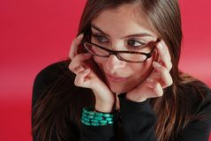 Woman in glasses. Beautiful girl showing off her glasses on a red background Stock Photo