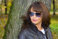 Woman in glasses. A woman in leather and dark glasses Courte stands against the backdrop of a tree trunk. A shot taken in the fall woods Stock Photography