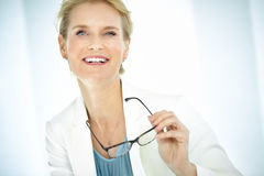 Woman With Glasses. Beautiful smiling elegant woman indoors wearing business attire, white blazer and short blond hair. Professional woman holding glasses Royalty Free Stock Photos