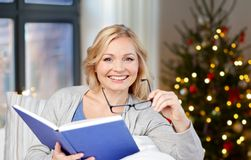 Woman with glasses and book on christmas at home royalty free stock photography